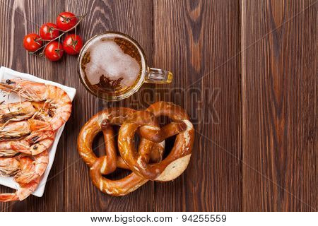 Pretzel, beer mug and grilled shrimps on wooden table. Top view with copy space