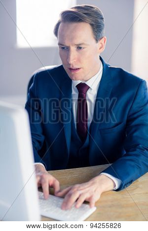 Serious businessman typing on computer in his office