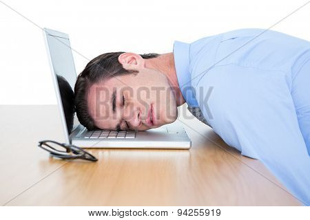exhausted businessman sleeping head on laptop against a white wall