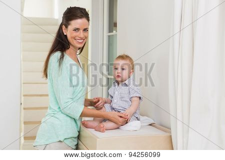 Happy mother with her baby boy at home