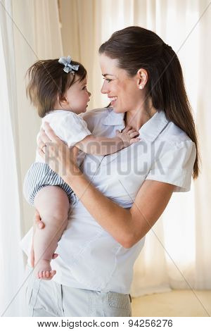 Happy mother with her cute baby girl at home