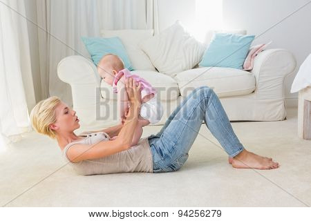 Happy mother with her baby girl at home in the living room