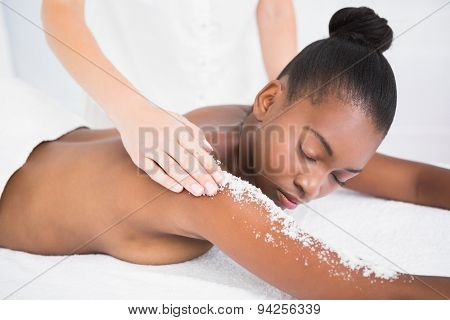 Pretty woman enjoying an exfoliation massage at the health spa