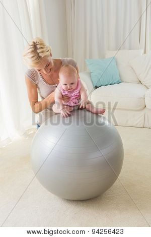 Happy mother with her baby girl on the exercice ball at home in the living room