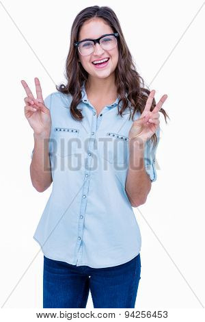 Pretty geeky hipster making peace sign on white background