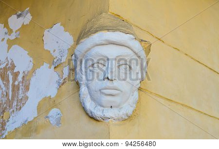 Plaster sculpture of a man's face positioned on the corner of the house
