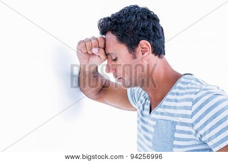 Sad man leaning his head against a wall on white background