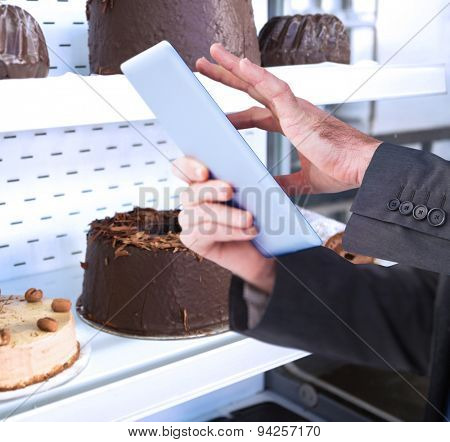 Businessman scrolling on his digital tablet against close up of desert like swiss roll and coffee cake