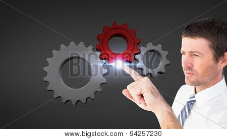 Businessman pointing with his finger against grey vignette