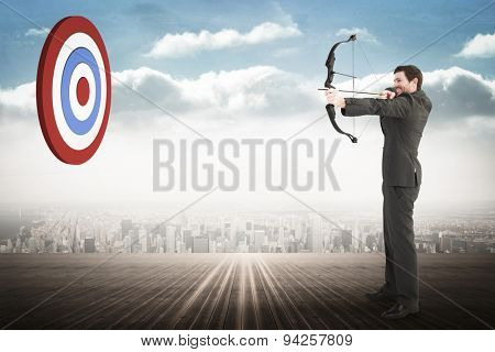 Businessman shooting a bow and arrow against city on the horizon