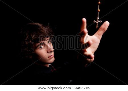 Young Men With Arm Raised, Trying To Grab A Crucifix, Isolated On Black, Studio Shot