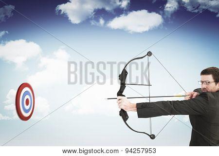 Businessman shooting a bow and arrow against blue sky