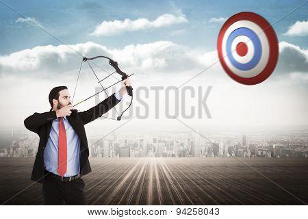 Focused businessman shooting a bow and arrow against city on the horizon