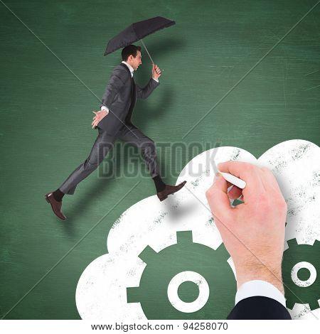 Businessman jumping holding an umbrella against green chalkboard
