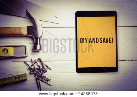 The word diy and save! and tablet pc against tablet displaying blueprint
