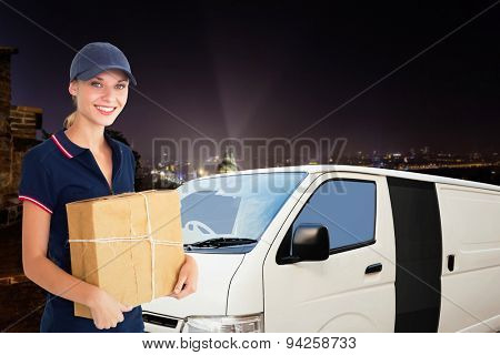 Happy delivery woman holding cardboard box against cityscape by night