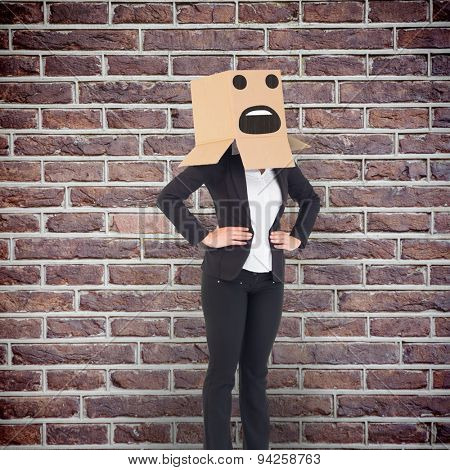 Businesswoman with box over head against red brick wall