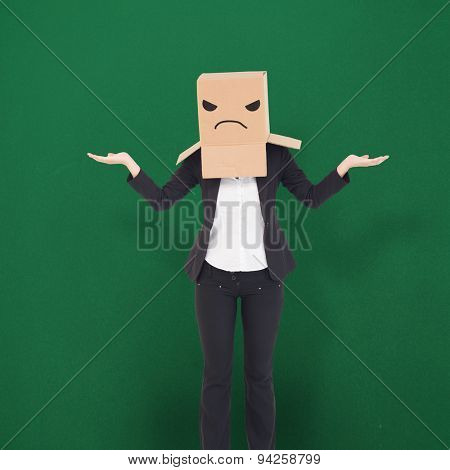 Businesswoman with box over head against green