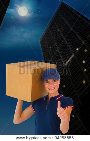 Happy delivery woman holding cardboard box showing thumbs up against city at night