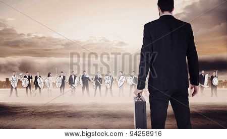Rear view of businessman holding a briefcase against large city on the horizon