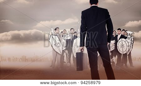 Rear view of businessman holding a briefcase against city on the horizon