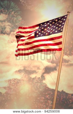 Digitally generated american national flag against colourful fireworks exploding on black background