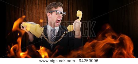 Geeky businessman shouting at telephone against wooden table