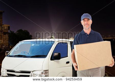Happy delivery man holding cardboard box against cityscape by night