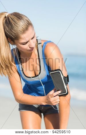 Portrait of beautiful fit woman using her phone at the beach