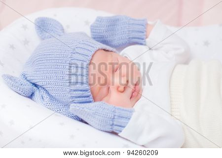 Sleeping Little Baby Wearing Knitted Blue Hat With Ears And Mittens Lying In Beautiful Cradle