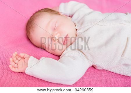 Cute Little Baby With Closed Eyes Wearing Knitted White Clothes Lying On Pink Plaid, 2 Week Old Baby