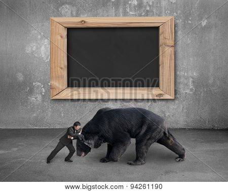 Businessman Fighting Against Black Bear With Blank Blackboard