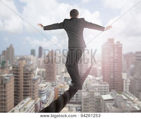 Businessman Balancing On A Wire With Sky Clouds Cityscape