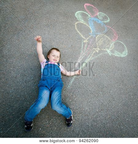 Little Girl with balloons, drawing with chalk on the pavement