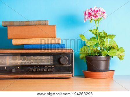 Old radio with flower and books, vintage still life