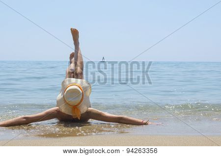 Girl Lying On The Beach With Legs Lifted Up