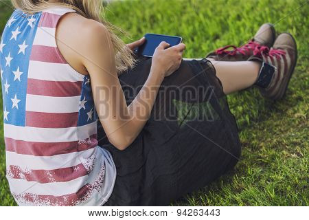Female Model Against A Lawn In A T-shirt With An American Flag And A Phone
