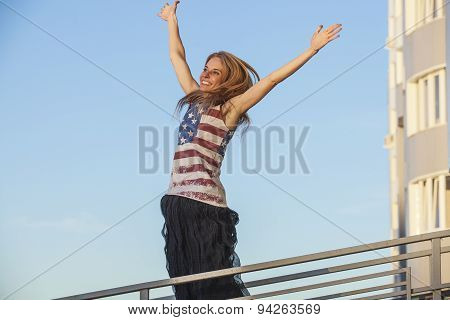 Female Model On The Background Of Sky In A T-shirt With The American Flag