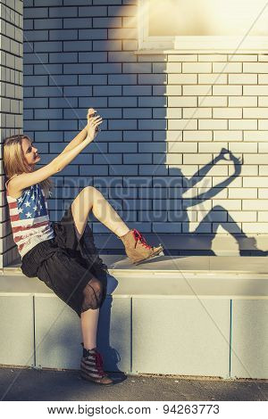 Female Model On The Background Of A Building In A T-shirt With An American Flag And A Phone