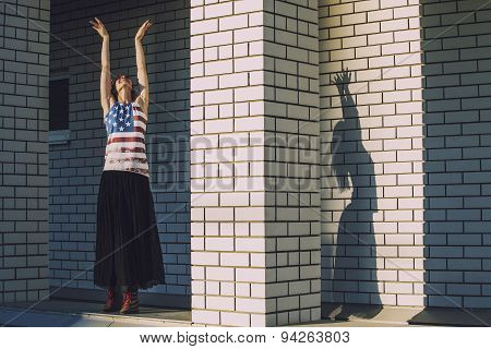 Female Model On The Background Of A Building In A T-shirt With An American Flag