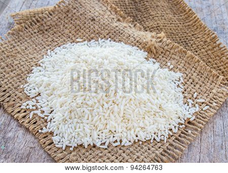 Rice Grains On Burlap Sack Background