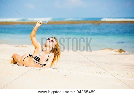 Sexy happy blond young female in sunglasses taking selfie on the beach enjoying summer holidays. Tra