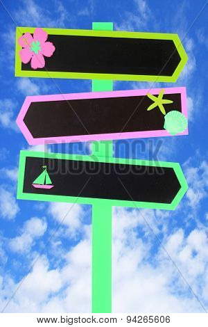 Colorful beach themed direction chalk board signs against a blue sky. Add your own text.