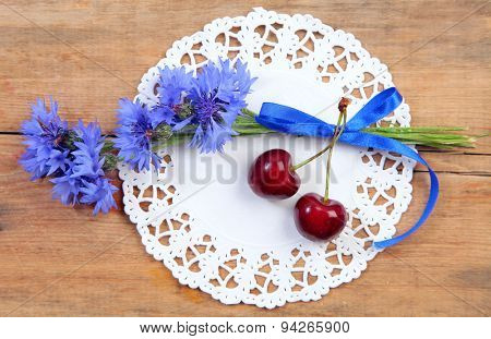sweet cherry and flowers on wood
