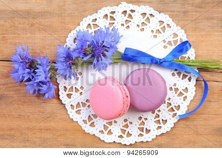 sweet macaroon and flowers on wood