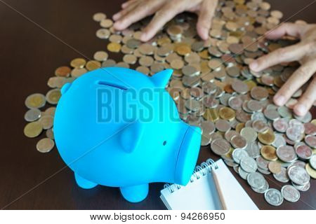 Man Hand Collect The Money Coin Into Blue Piggy Bank