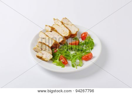 plate of sliced chicken breasts with rucola and cherry tomatoes on white background