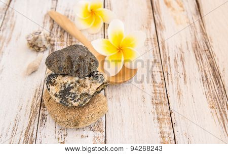Stone Therapy And Tropical Plumeria On Wooden Table