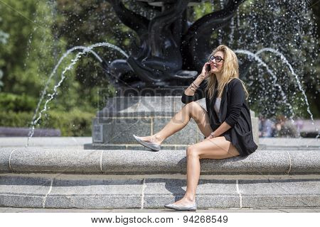Young attractive blonde woman sitting on the curb of the fountain talking on the cell phone.