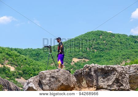 Male Photographer With Photo Camera On Tripod Stands On Stones In Meteors, Greece